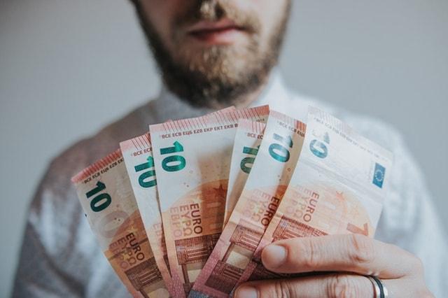 Um homem segura 6 notas de dez euros na mão.