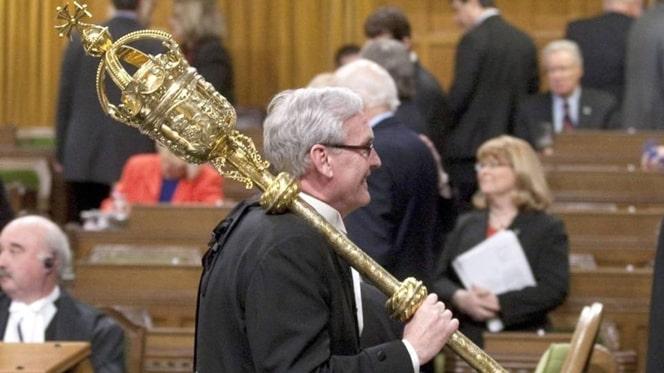O imagem mostra um senhor segurando a maça cerimonial britânica.
